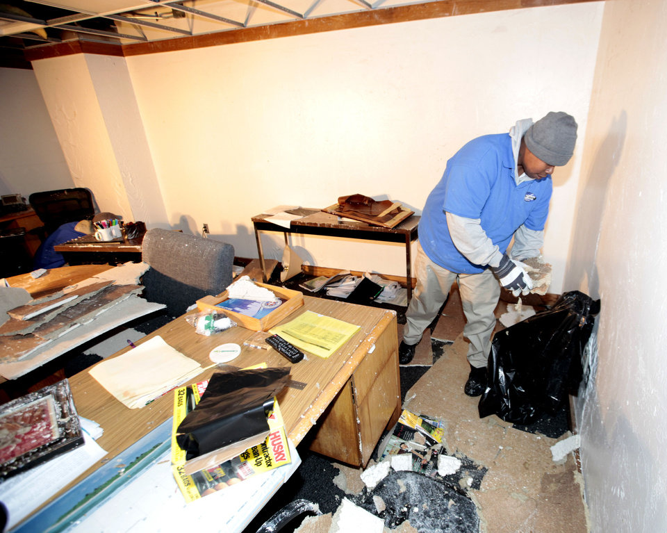 Photo - Steven Green picks up debris in one of the flooded city offices in the basement of the  building at 420 West Main, Monday, February 3, 2014. Photo by David McDaniel, The Oklahoman