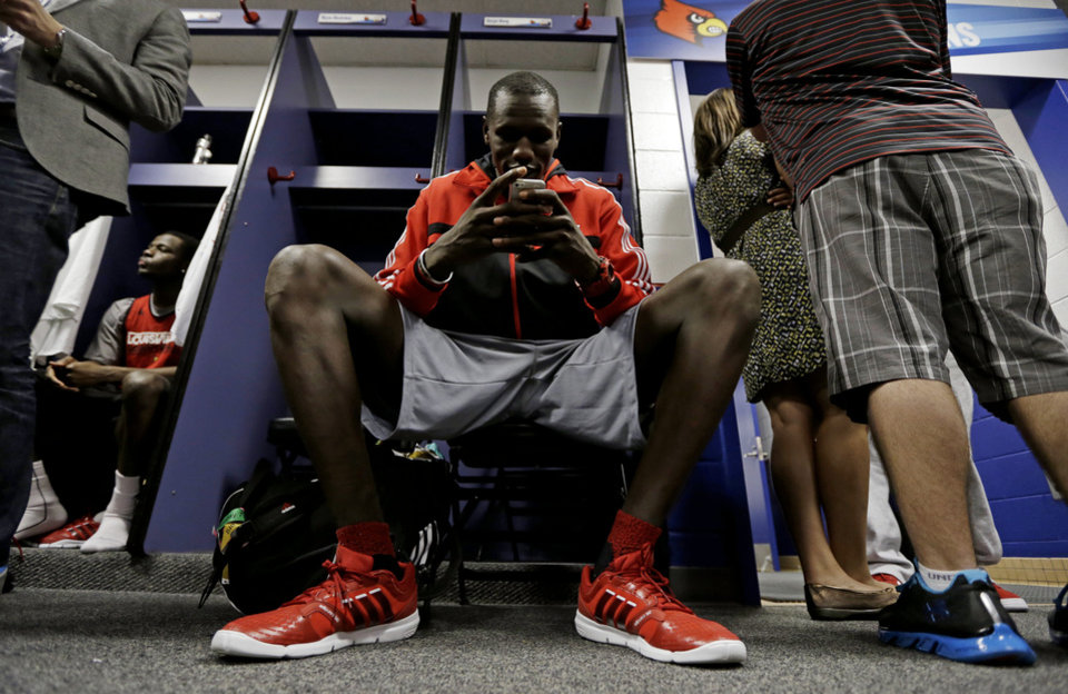 Photo - Louisville's Gorgui Dieng looks at his phone in the locker room before practice for their NCAA Final Four tournament college basketball game Sunday, April 7, 2013, in Atlanta. Louisville plays Michigan in the championship game on Monday. (AP Photo/Charlie Neibergall)  Charlie Neibergall