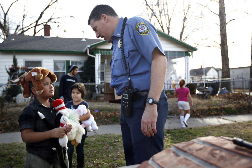 Lt. Keith Castillo talks with Tristan Frias, 7, after receiving toys from Oklahoma City firefighters in Oklahoma City, Saturday, Dec. 24, 2011. Photo by Sarah Phipps, The Oklahoman