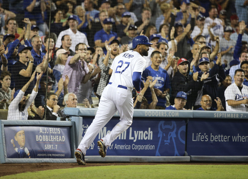 Photo - Los Angeles Dodgers' Matt Kemp runs toward the dugout after scoring on a sacrifice fly by Scott Van Slyke during the sixth inning of a baseball game against the Los Angeles Angels on Tuesday, Aug. 5, 2014, in Los Angeles. (AP Photo/Jae C. Hong)