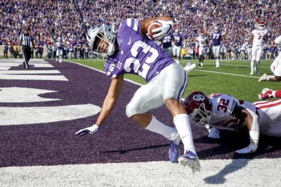 Photo -  Kansas State wide receiver Joshua Youngblood scores a touchdown against OU and Sooners' safety Delarrin Turner-Yell during Saturday's game in Manhattan, Kan. The Wildcats scored six rushing touchdowns in their win, including this one from Youngblood. [Ian Maule/Tulsa World via AP]