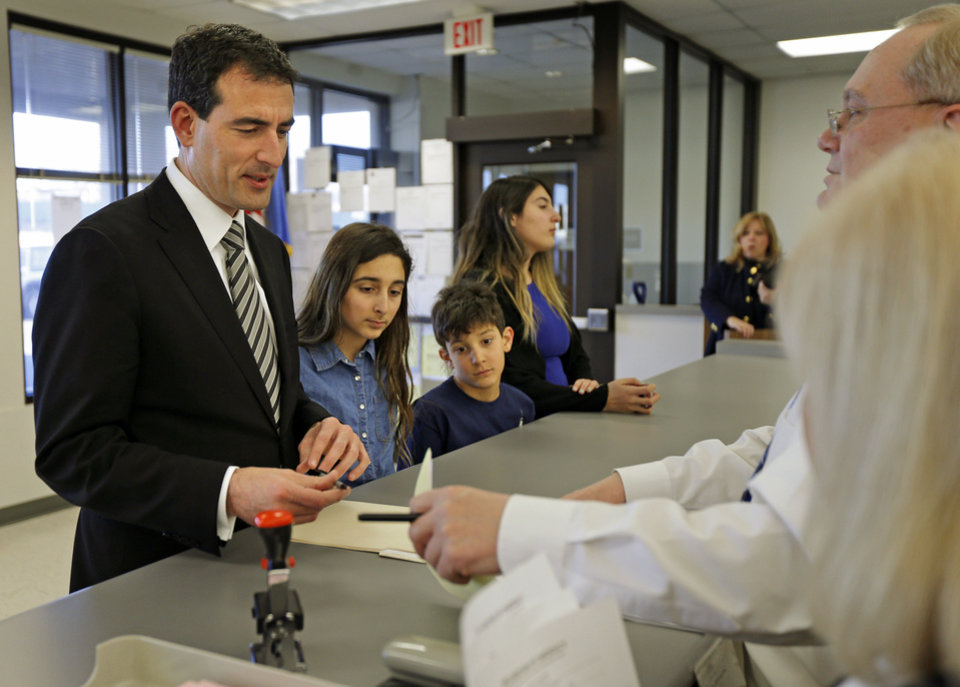 Photo - Oklahoma City mayoral candidate Ed Shadid files paperwork for his candidacy beside his children Dahlia, 10, left, Zane, 9, and Maya, 12, inside the Oklahoma County Election Board offices on Wednesday, January 29, 2014. Photo by Bryan Terry, The Oklahoman