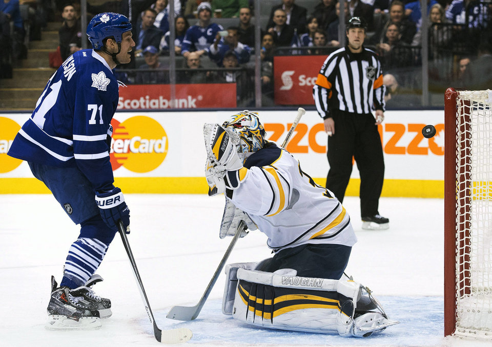 Photo - Buffalo Sabres goalie Ryan Miller gets scored on as Toronto Maple Leafs forward David Clarkson, left, looks on during the second period of an NHL hockey game, Wednesday, Jan. 15, 2014 in Toronto. (AP Photo/The Canadian Press, Nathan Denette)