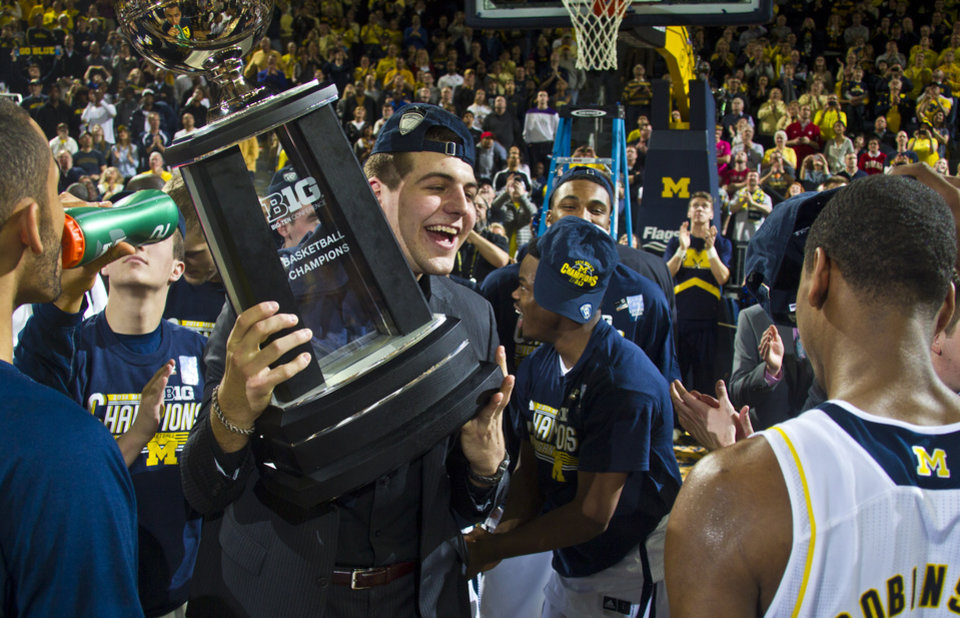 Photo - Michigan forward Mitch McGary holds the Big Ten Conference Basketball Champions trophy in celebration with teammates on the court after an NCAA college basketball game against Indiana at Crisler Center in Ann Arbor, Mich., Saturday, March 8, 2014. Michigan won 84-80, and celebrated their outright Big Ten regular season championship. (AP Photo/Tony Ding)