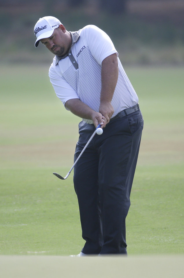 Photo - Brendon De Jonge, of Zimbabwe, chips to the green on the seventh hole during the second round of the U.S. Open golf tournament in Pinehurst, N.C., Friday, June 13, 2014. (AP Photo/Eric Gay)