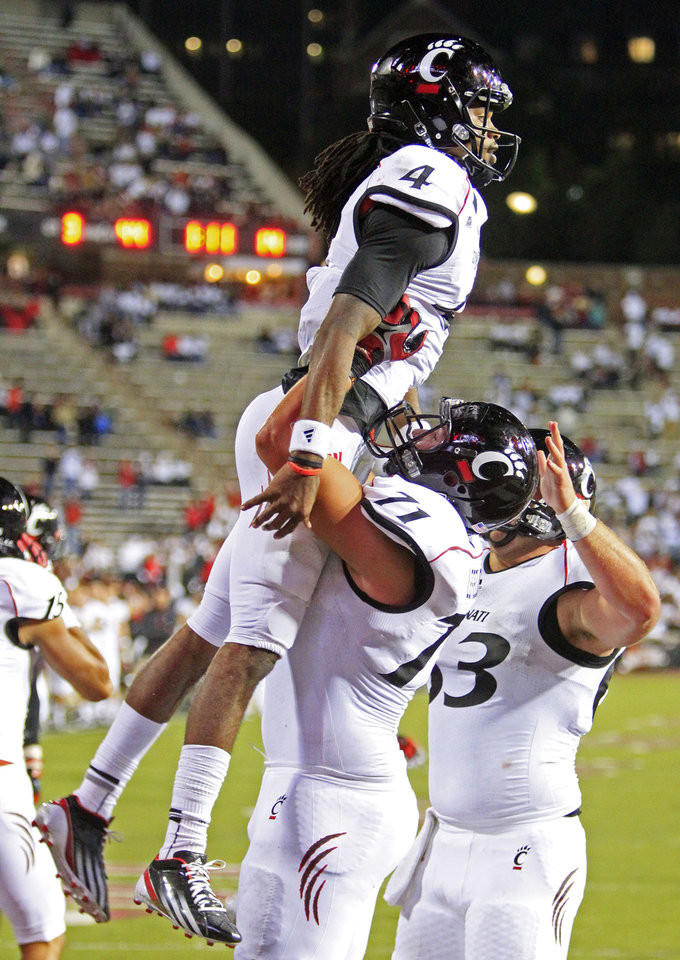 Cincinnati tackle Eric Lefeld (71) lifts quarterback Munchie Legaux (4) after Legaux scored on a 1-yard touchdown run in the second half of an NCAA college football game against Miami (Ohio), Saturday, Oct. 6, 2012, in Cincinnati. (AP Photo/Al Behrman)