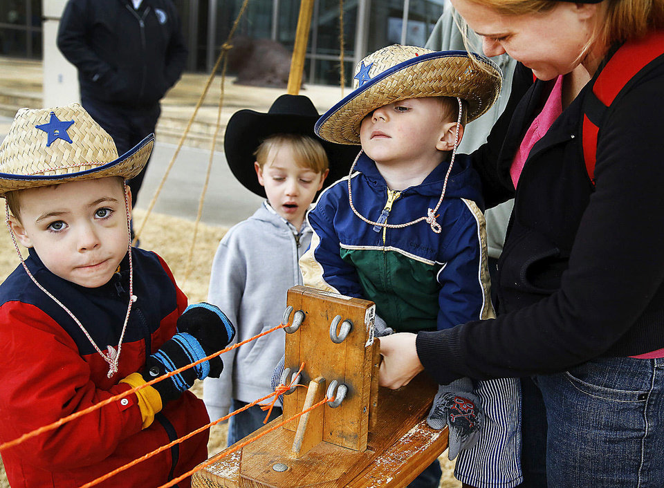 Larkin Corry, 2, gets help from his mother, Christina Corry, of Midwest City, as they make a section of braid. Waiting his turn to make a rope during Saturday's Cowboy Round-up at the Oklahoma History Center is older brother Kian, 4, at left. In background is Kenton Billings, 5, of Norman. Photo by Jim Beckel, The Oklahoman