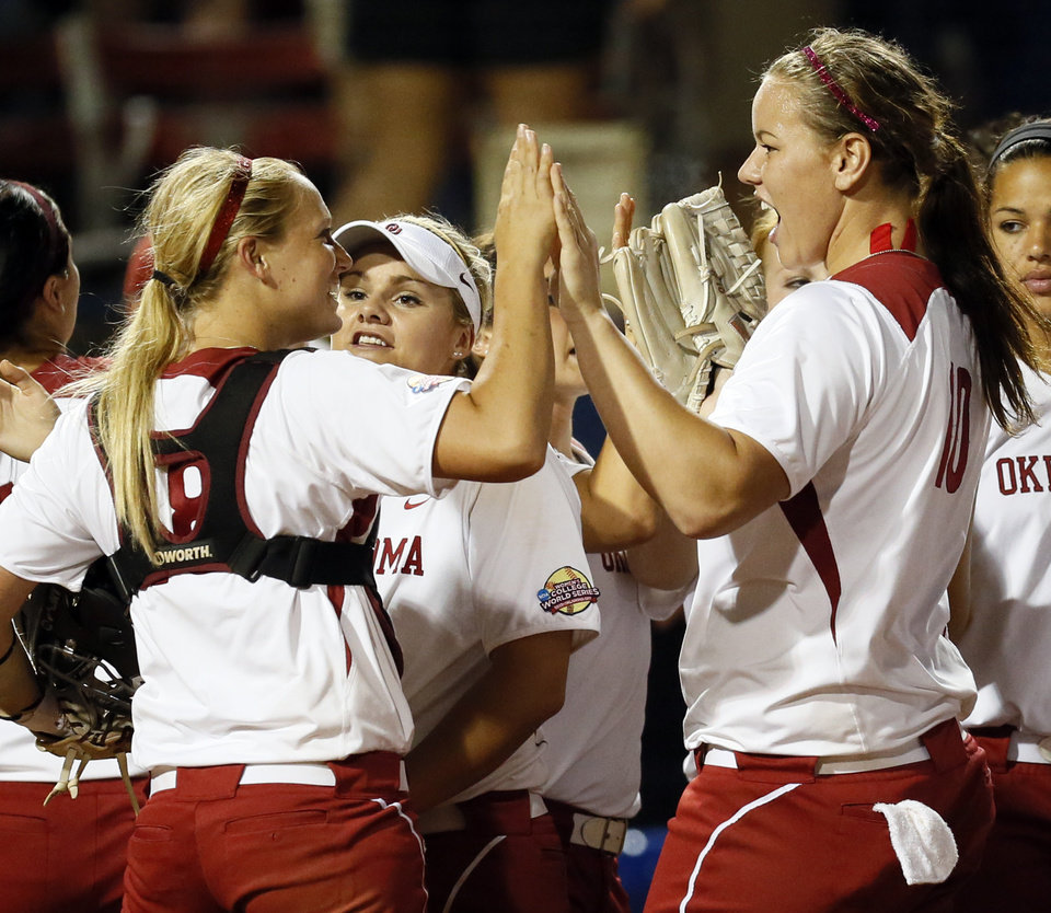 Photo - OU catcher Jessica Shults (18), left, and pitcher Keilani Ricketts (10) celebrate with the rest of the Sooners after an NCAA softball game in the Women's College World Series between Oklahoma and Michigan at ASA Hall of Fame Stadium, Thursday, May 30, 2013. OU won, 7-1. Photo by Nate Billings, The Oklahoman