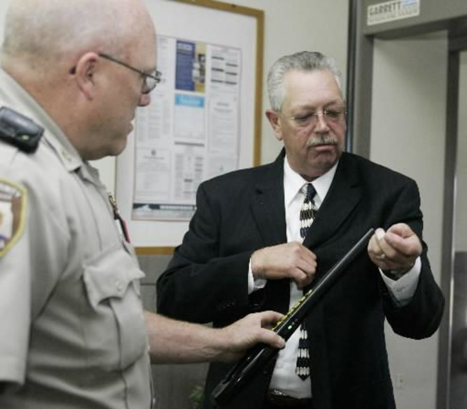 Photo - Former Custer County Sheriff  Mike  Burgess, right, is checked through security by Custer County Deputy Sheriff Larry Cornelsen, left, as he enters the courthouse in Arapaho, Okla. on Tuesday, Aug. 12, 2008.  Burgess, 55, faces 35 felony charges, including 14 counts of second-degree rape, seven counts of forcible oral sodomy and five counts of bribery by a public official. (AP Photo)