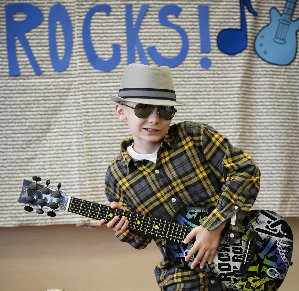 Photo - Dylan Hill rocks out with a guitar on Thursday as he walks the red carpet during the Camp Noggin talent show at Youth and Family Services in El Reno , Okla. on Thursday, June 5, 2014 . The camp lets children with autism have a place to take part in summer activities.  Photos by Chris Landsberger,   The Oklahoman   CHRIS LANDSBERGER - CHRIS LANDSBERGER