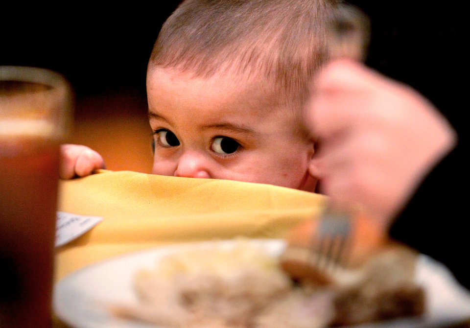 Photo - Jayden Romero, 14 months, watches as his mother, Sarah, of Edmond, gets a piece of turkey for him at the 30th Edmond Community Thanksgiving Dinner in the George Nigh Student Center on the campus of University of Central Oklahoma, Thursday,  Nov. 24, 2011.  Photo by Jim Beckel, The Oklahoman