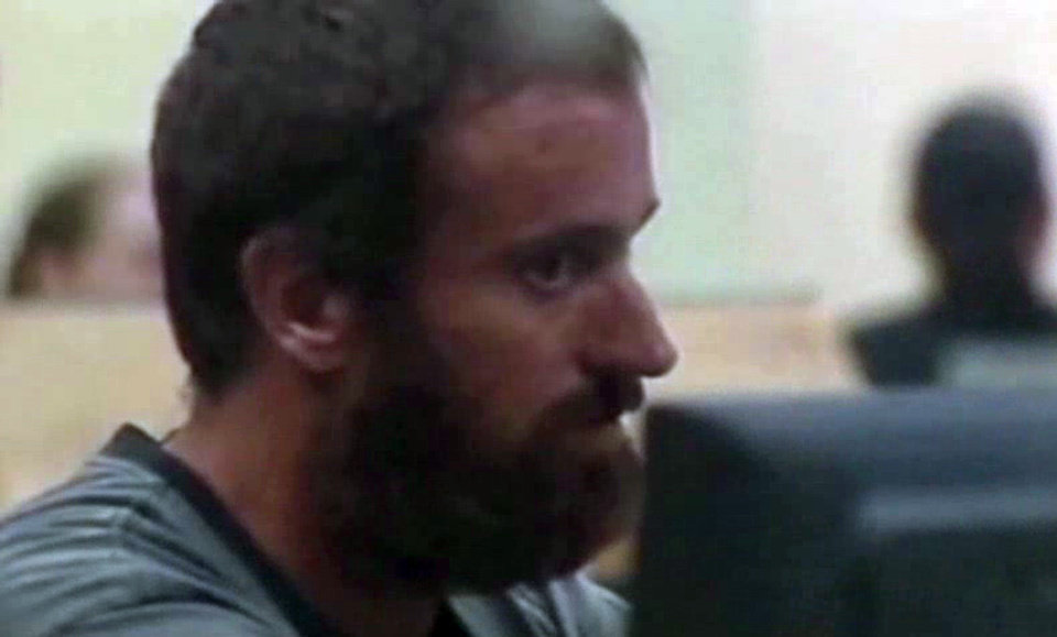 This framegrabbed image provided by Baynews9 shows Joshua Michael Hakken being processed for booking into the Hillsbourgh County Jail early Wednesday morning April 10, 2013. The Florida couple accused of kidnapping their two young sons and fleeing by boat to Havana were handed over to the United States, and were booked into a Florida jail, officials said Wednesday. (AP Photo/Baynews9, Pool)