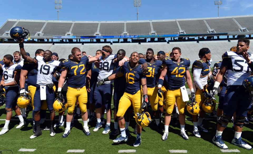 Photo - West Virginia players wave at the crowd and sing