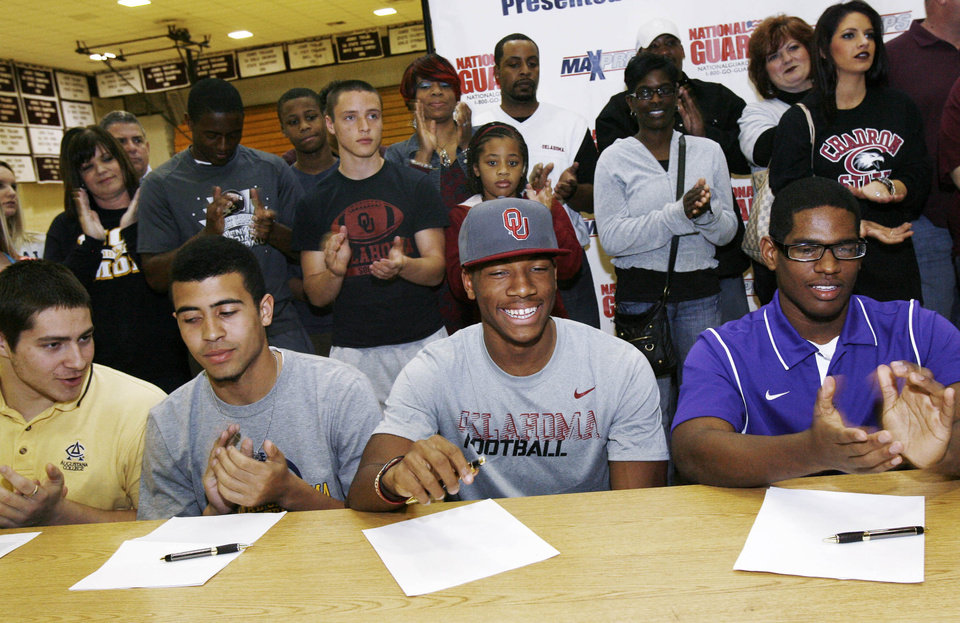 Photo - Members of the Jenks high school football team including Nick Lucido (left), Taylor Hunter, Jordan Smallwood, and Jeff Scallion, taken during signing Day in Jenks, Okla., on February 6,2013. JAMES GIBBARD/Tulsa World