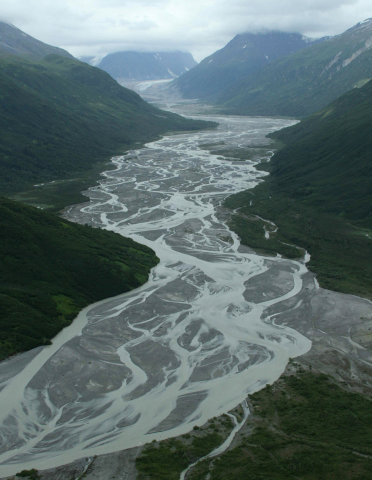Photo - This photo taken July 5, 2013, in Lake Clark Pass near Port Alsworth, Alaska, shows a river valley cutting through the mountains. Many float planes will fly through the pass as they take day-trippers to Katmai National Park and Preserve to see the brown bears. (AP Photo/Mark Thiessen)