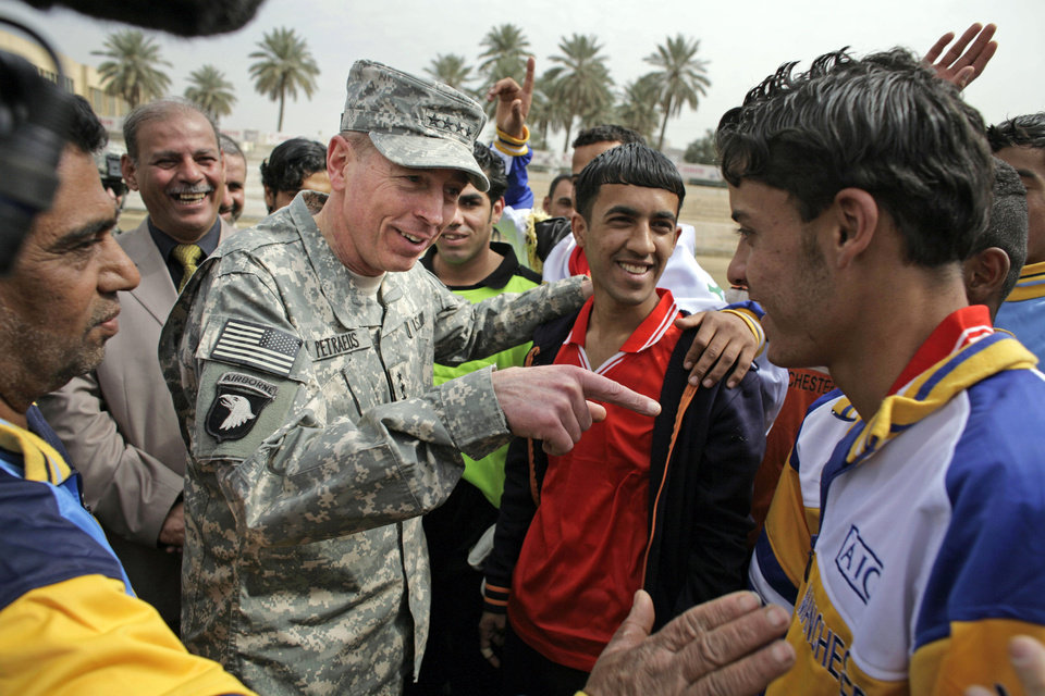 Photo -   FILE - In this March 1, 2008 file photo, then-top U.S. commander in Iraq, Gen. David Petraeus, center left, talks to players during a youth soccer tournament in central Baghdad, Iraq. Petraeus, the retired four-star general who led the U.S. military campaigns in Iraq and Afghanistan, resigned Friday, Nov. 9, 2012 as director of the CIA after admitting he had an extramarital affair. (AP photo/Dusan Vranic, File)