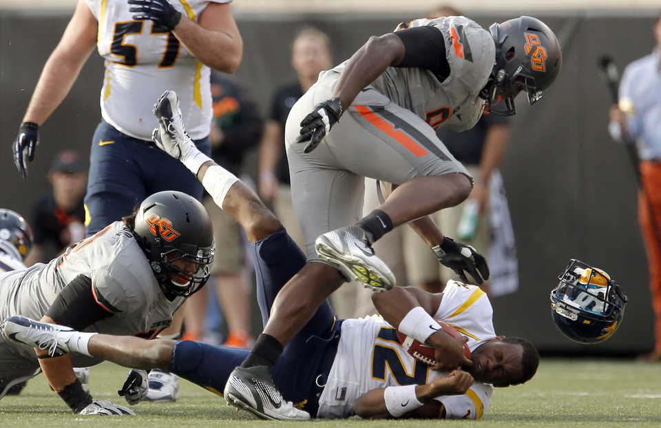 Photo - Oklahoma State's Christian Littlehead (72) and Oklahoma State's Ryan Robinson (96) sack West Virginia's Geno Smith (12) during a college football game between Oklahoma State University (OSU) and the West Virginia University at Boone Pickens Stadium in Stillwater, Okla., Saturday, Nov. 10, 2012. Photo by Sarah Phipps, The Oklahoman