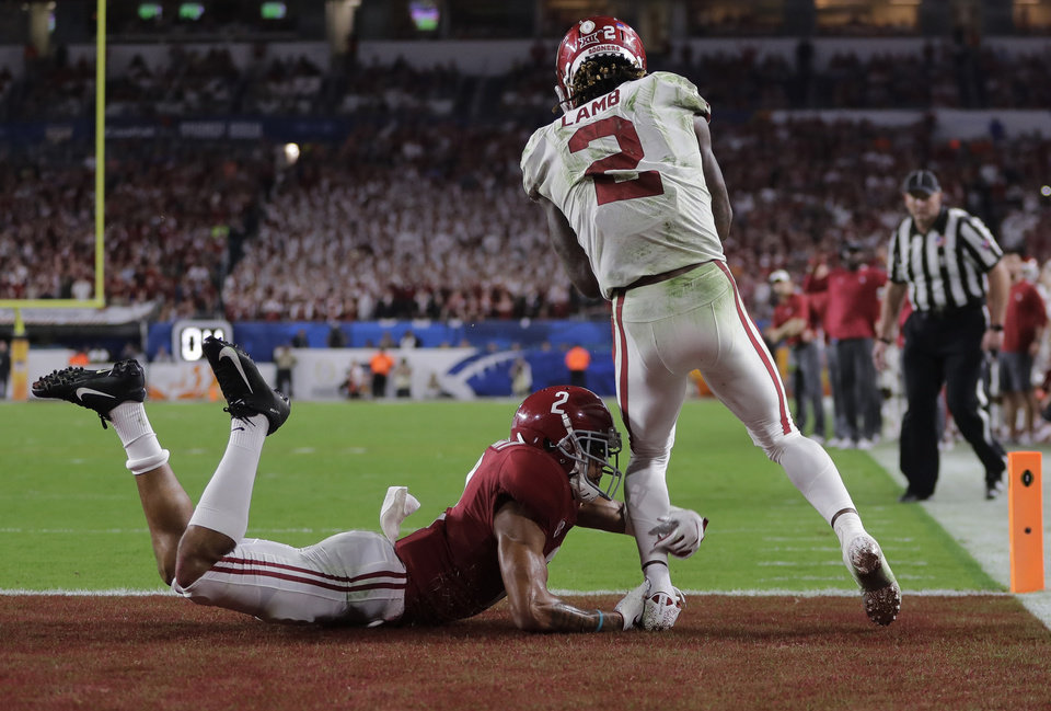 Photo - Oklahoma wide receiver CeeDee Lamb (2) scores a touchdown as Alabama defensive back Patrick Surtain II (2) grabs his leg, during the second half of the Orange Bowl NCAA college football game, Saturday, Dec. 29, 2018, in Miami Gardens, Fla. (AP Photo/Lynne Sladky)