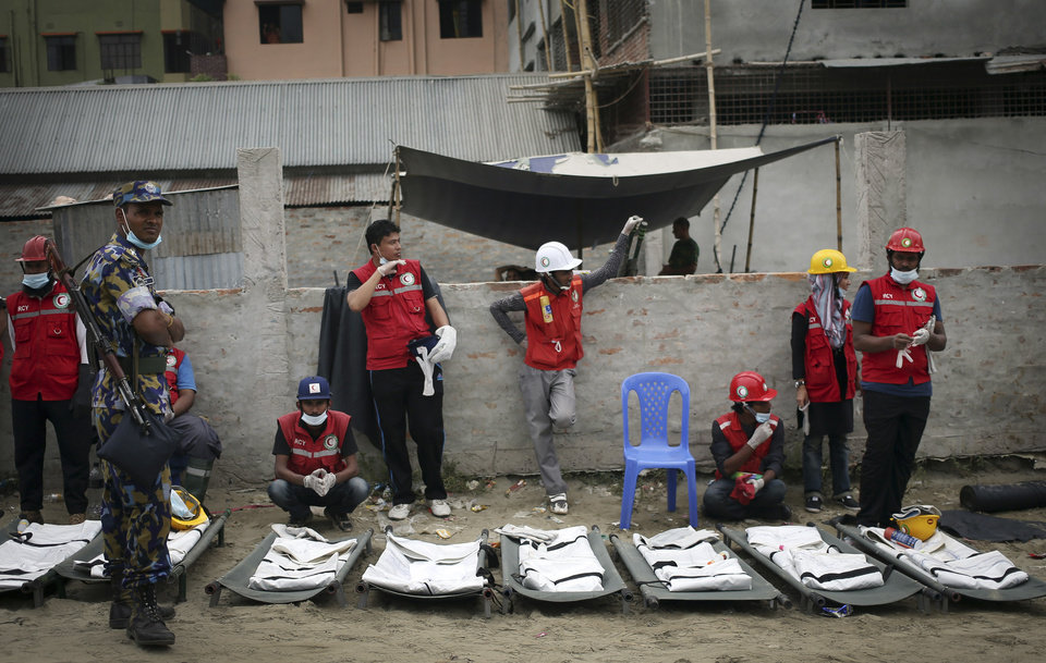 Photo - Health volunteers wait next to body bags lined up as they prepare to extract more dead bodies while workers start dislodging parts of the garment factory building which collapsed in Savar, near Dhaka, Bangladesh on Monday April 29, 2013. Rescue workers in Bangladesh gave up hopes of finding any more survivors in the remains of a building that collapsed five days ago, and began using heavy machinery on Monday to dislodge the rubble and look for bodies - mostly of workers in garment factories there. At least 381 people were killed when the illegally constructed, 8-story Rana Plaza collapsed in a heap on Wednesday morning along with thousands of workers in the five garment factories in the building.(AP Photo/Wong Maye-E)