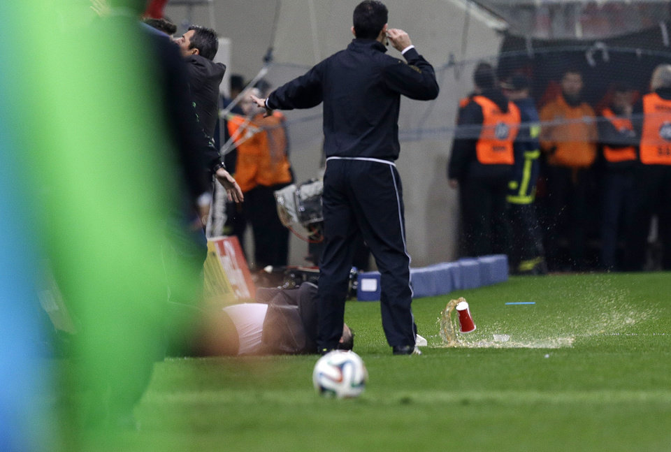 Photo - Panathinaikos' coach Giannis Anastasiou lays on the grass after being hit by a plastic cup during a Greek League soccer match against Olympiakos at Georgios Karaiskakis stadium, in Piraeus port, near Athens, on Sunday, March 2, 2014. (AP Photo/Thanassis Stavrakis)