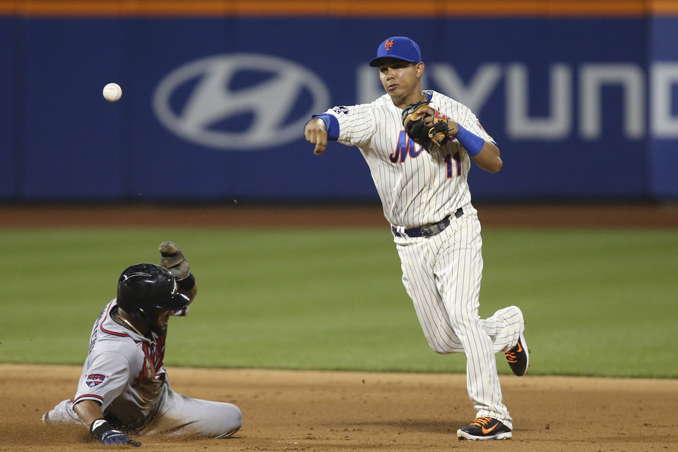 Photo - New York Mets shortstop Ruben Tejada (11) turns a double play as Atlanta Braves' Emilio Bonifacio, left, slides into second base in the ninth inning of a baseball game, Wednesday, Aug. 27, 2014, in New York. The Braves won 3-2. (AP Photo/John Minchillo)