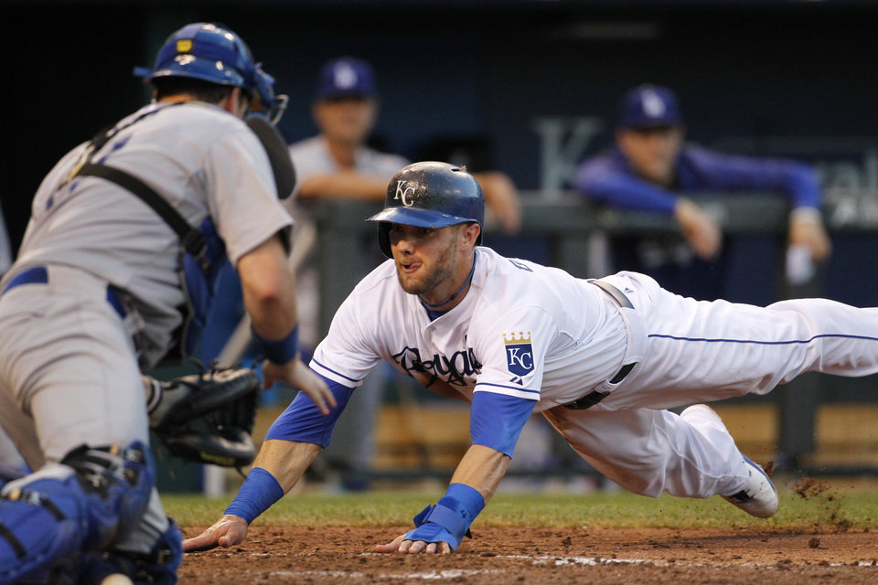 Photo - Kansas City Royals' Alex Gordon dives into home plate to score as Los Angeles Dodgers catcher A.J. Ellis is unable to make the tag in the fourth inning of a baseball game at Kauffman Stadium in Kansas City, Mo., Wednesday, June 25, 2014.  (AP Photo/Colin E. Braley)