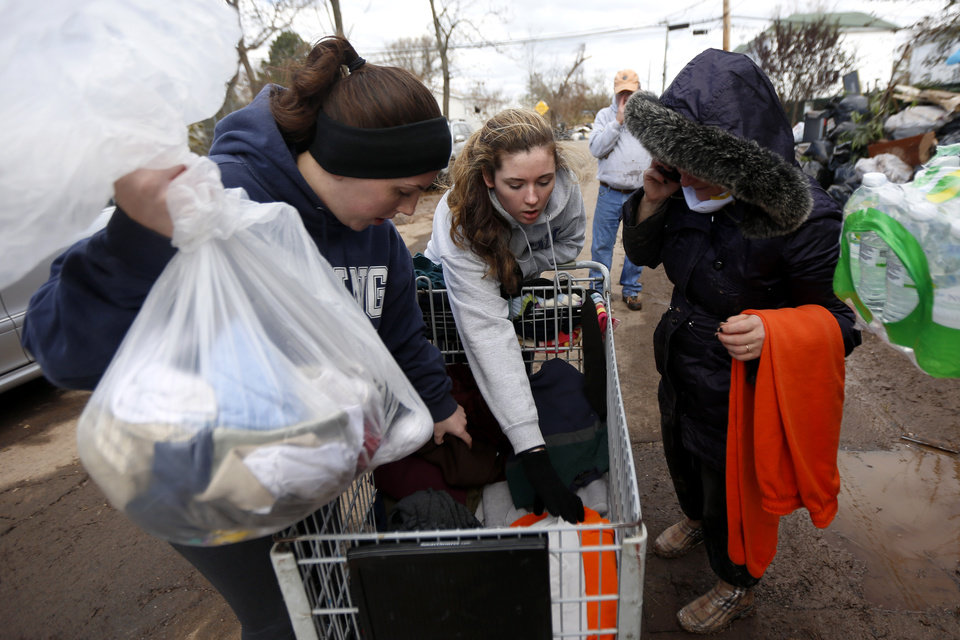 Photo -   Volunteers Laurie McLoughlin, left, and her sister Caitlin McLaughlin, center, sort through clothing to donate to a resident, Saturday, Nov. 3, 2012, in Staten Island, N.Y. A Superstorm Sandy relief fund is being created just for residents of the hard-hit New York City borough. Former Mayor Rudolph Giuliani and Borough President James Molinaro say the fund will help residents displaced from their homes. (AP Photo/Julio Cortez)