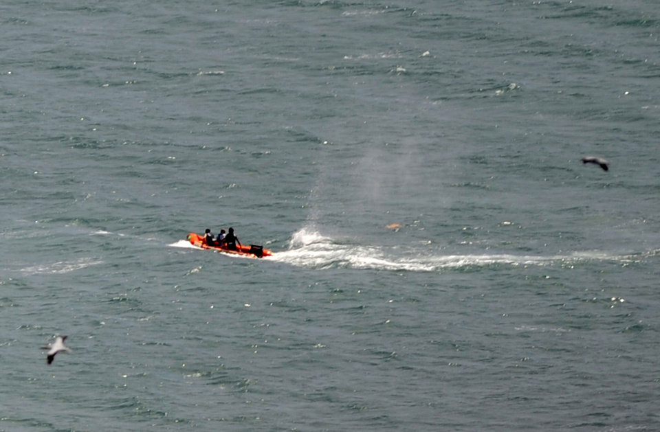 Photo - Police in inflatable rubber boats shoot at a shark off Muriwai Beach near Auckland, New Zealand, Wednesday, Feb. 27, 2013, as they attempt to retrieve a body following a fatal shark attack. Police said a man was found dead in the water after being