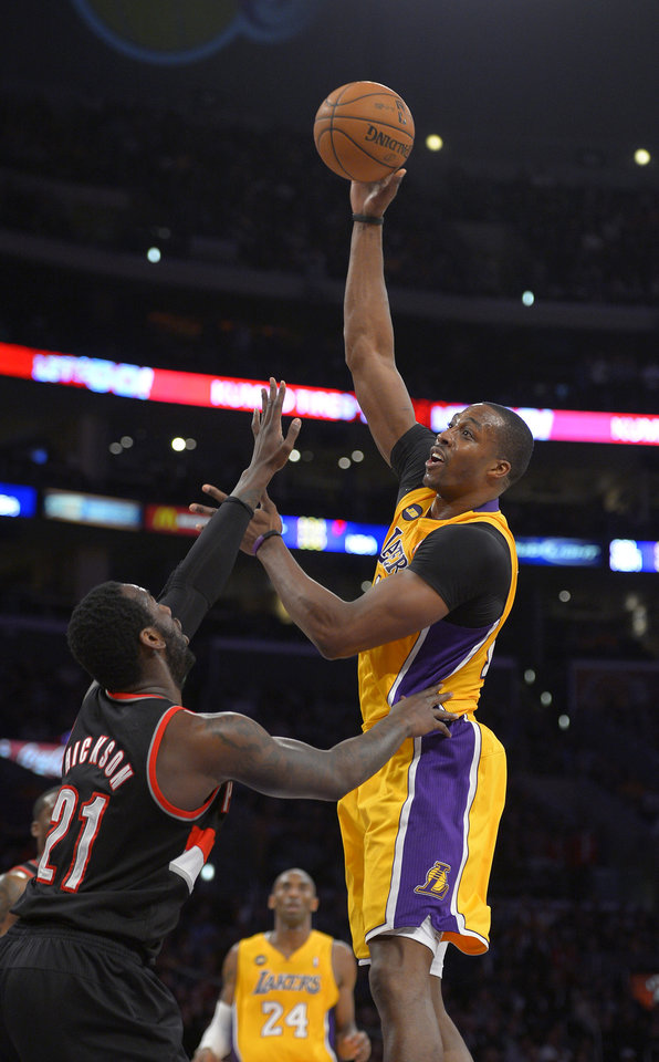 Photo - Los Angeles Lakers center Dwight Howard, right, puts up a shot as Portland Trail Blazers center J.J. Hickson defends during the first half of their NBA basketball game, Friday, Feb. 22, 2013, in Los Angeles. (AP Photo/Mark J. Terrill)