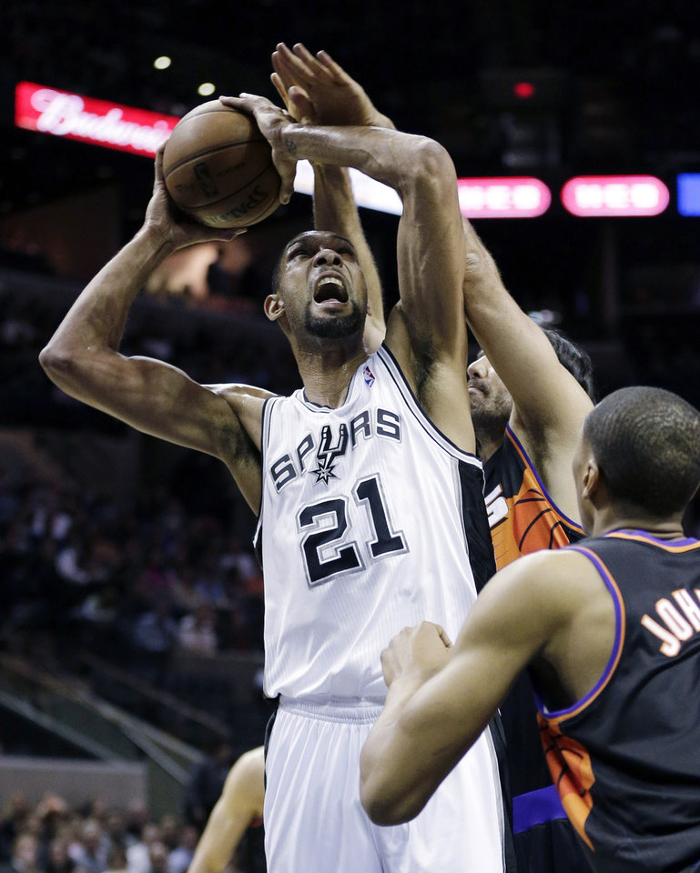 Photo - San Antonio Spurs' Tim Duncan (21) is fouled by Phoenix Suns' Luis Scola, rear, of Argentina, during the first half of an NBA basketball game, Wednesday, Feb. 27, 2013, in San Antonio. Suns' Wesley Johnson, right, also defends on the play. (AP Photo/Eric Gay)