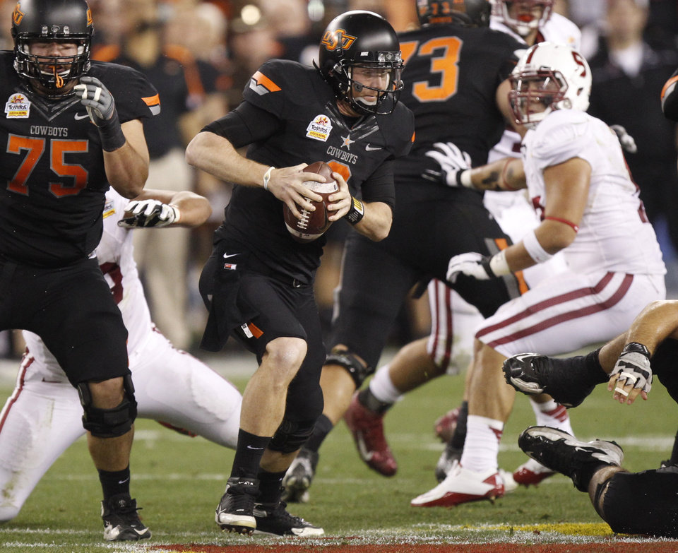 Photo - Oklahoma State quarterback Brandon Weeden (3) scrambles against  Stanford during the first half of the Fiesta Bowl NCAA college football game Monday, Jan. 2, 2012, in Glendale, Ariz. (AP Photo/Paul Connors)