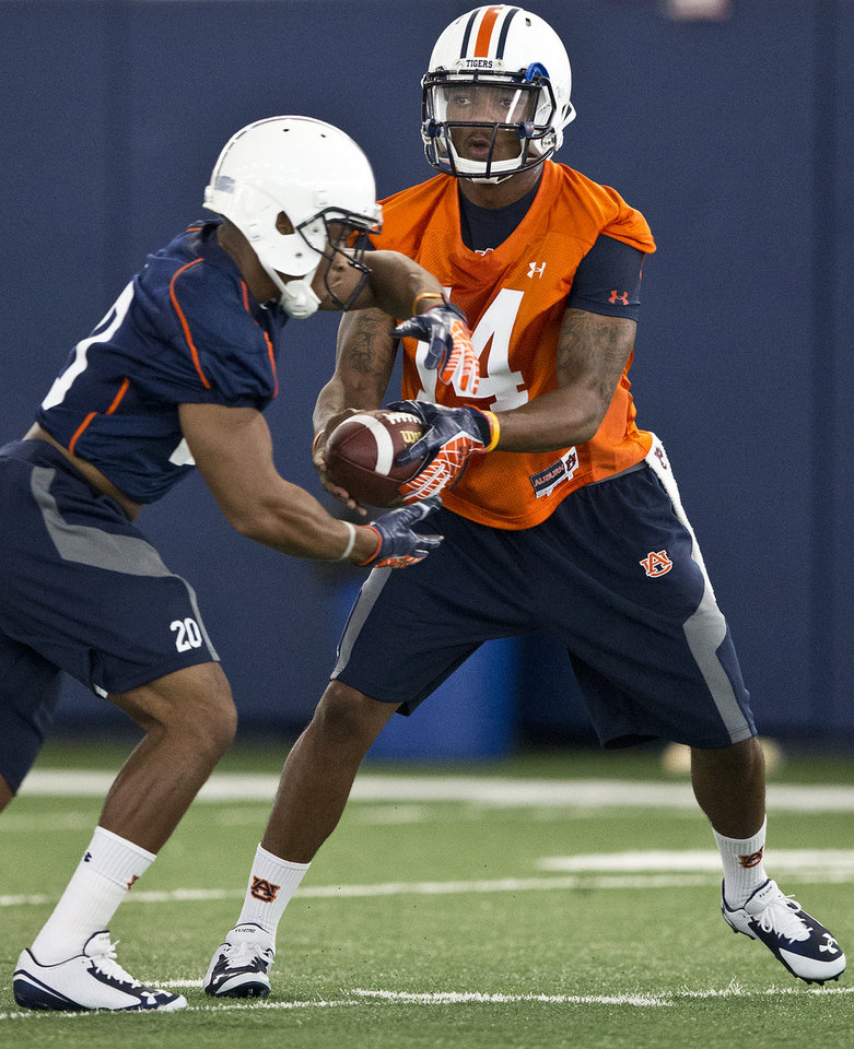 Photo - Auburn quarterback Nick Marshall, right, runs drills with running back Corey Grant during NCAA college football practice Friday, Aug. 1, 2014, in Auburn, Ala. (AP Photo/Brynn Anderson)