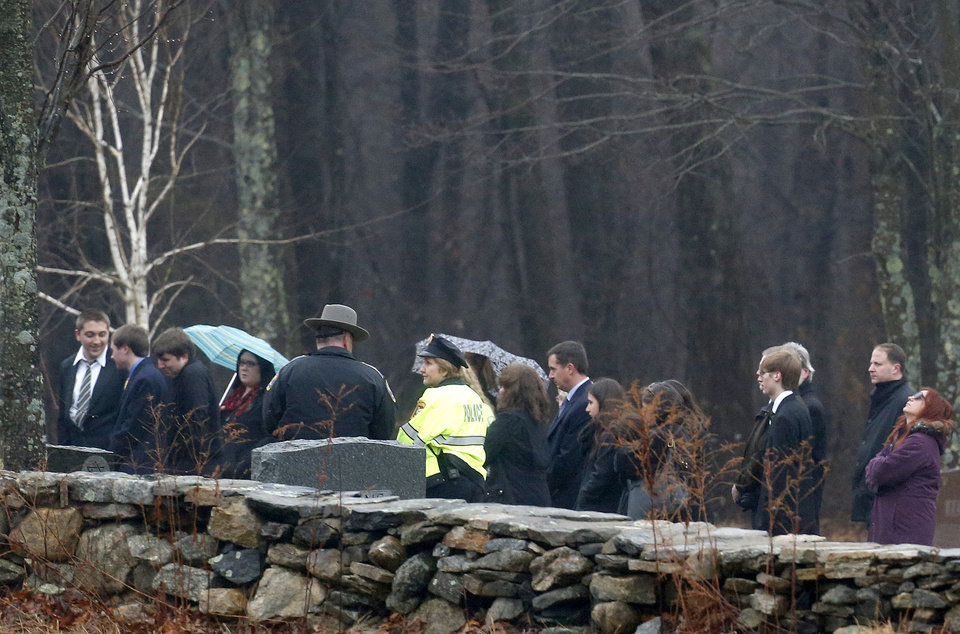 Photo - A woman, right, reacts during burial services at B'nai Israel Cemetery as Noah Pozner, a six-year-old killed in an elementary school shooting, was laid to rest, Monday, Dec. 17, 2012, in Monroe, Conn. Authorities say a gunman killed his mother at their home and then opened fire inside the Sandy Hook Elementary School in Newtown, killing 26 people, including 20 children, before taking his own life, on Friday. (AP Photo/Julio Cortez) ORG XMIT: CTJC128