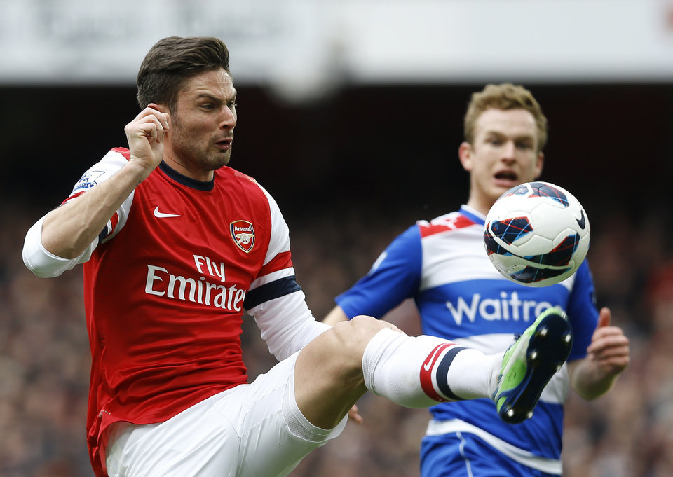 Arsenal's Olivier Giroud, left, vies for the ball with Reading's Alex Pearce during the English Premier League soccer match between Arsenal and Reading at the Emirates Stadium in London, Saturday, March 30, 2013. (AP Photo/Kirsty Wigglesworth)