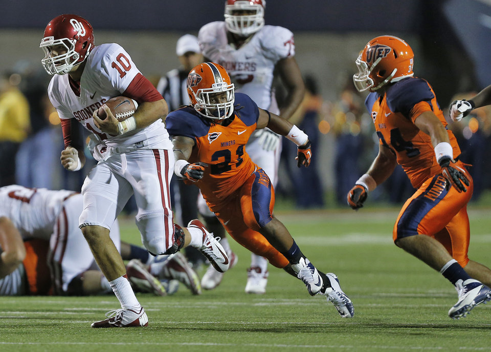 Photo - Oklahoma Sooners quarterback Blake Bell (10) runs past UTEP Miners defensive back Derrick Morgan (21) and UTEP Miners linebacker Anthony Puente (34) during the college football game between the University of Oklahoma Sooners (OU) and the University of Texas El Paso Miners (UTEP) at Sun Bowl Stadium on Sunday, Sept. 2, 2012, in El Paso, Tex.  Photo by Chris Landsberger, The Oklahoman
