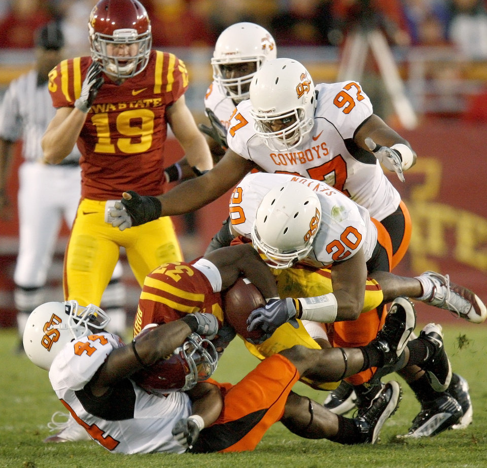 Photo - OSU's Donald Booker, at left, Andre Sexton, and Jermiah Price bring down Iowa State's Alexander Robinson as Iowa State's Josh Lenz watches during the college football game between the Oklahoma State University (OSU) Cowboys and Iowa State University (ISU) Cyclones at Jack Trice Stadium on Saturday, November 7, 2009, in Ames, Iowa. Photo by Bryan Terry, The Oklahoman ORG XMIT: KOD