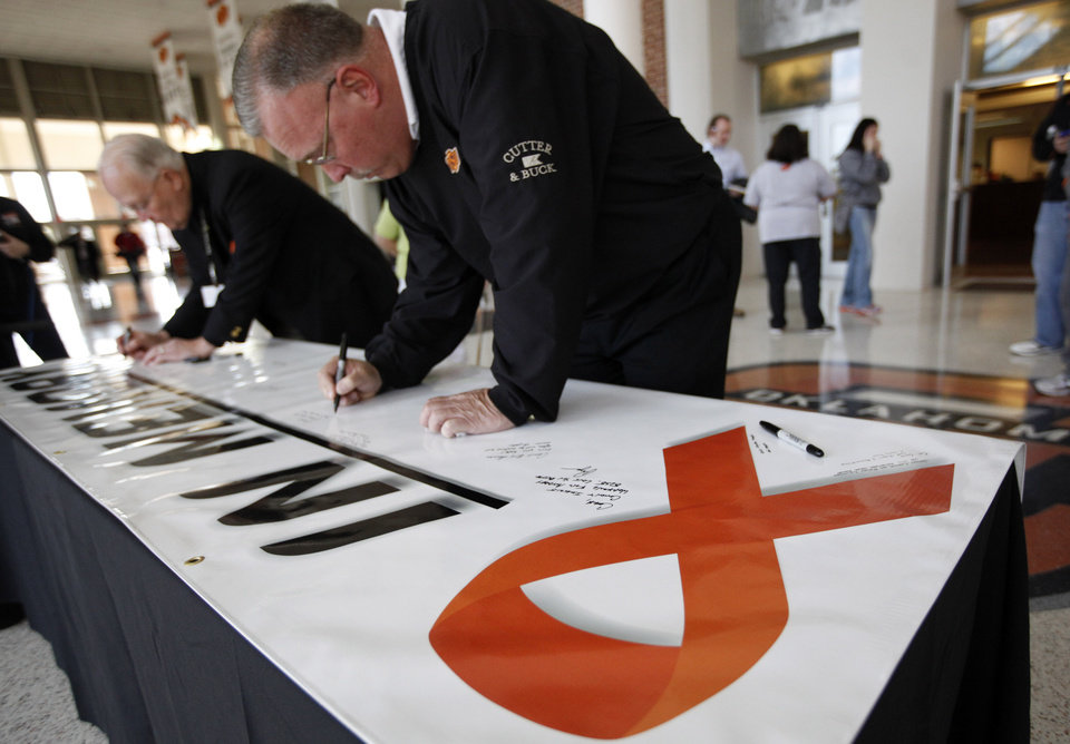 Associate head coach Jim Littell signs a memorial banner for OSU womens\' head coach Kurt Budke and assistant coach Miranda Serna at Gallagher- Iba Arena in Stillwater, Okla., Friday, Nov. 18, 2011. Photo by Sarah Phipps, The Oklahoman