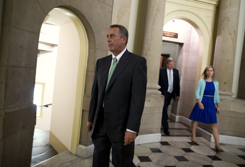 Photo - Speaker of the House Rep. John Boehner, R-Ohio, walks out of his office to the House Chamber on Tuesday, Oct. 1, 2013 in Washington. Congress plunged the nation into a partial government shutdown Tuesday as a protracted dispute over President Barack Obama's signature health care law reached a boiling point, forcing some 800,000 federal workers off the job.  (AP Photo/ Evan Vucci)