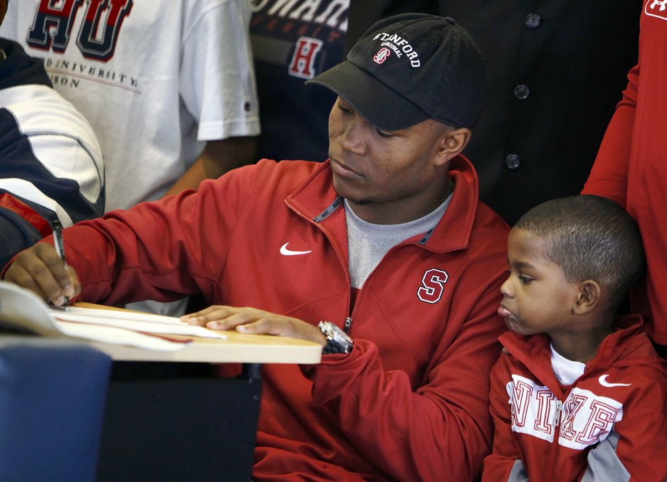 Photo - Heritage Hall's Barry J. Sanders signs to play football at Stanford as his little brother Terrance Johnson, 4, watches during the National Signing Day ceremony at Heritage Hall in Oklahoma City, Wednesday, Feb. 1, 2012. Photo by Nate Billings, The Oklahoman