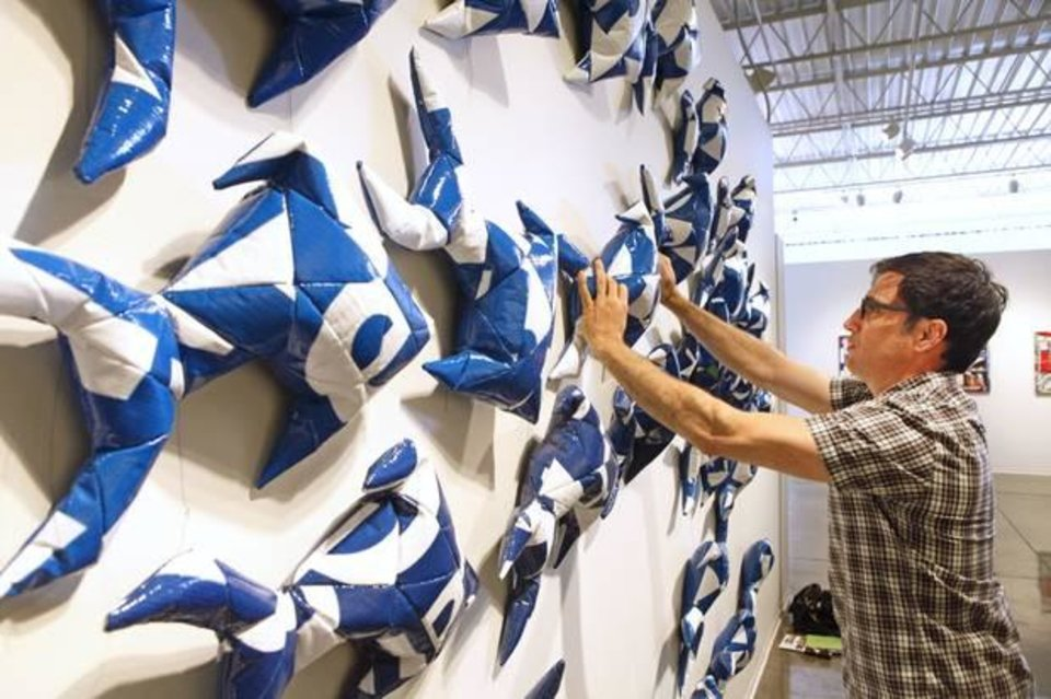 """Photo -  Dallas-based artist Jason Willaford installs vinyl fish he crafted from a reclaimed billboard into an installation titled """"In Business for Small Business"""" at Oklahoma Contemporary Arts Center. Photo by David McDaniel, The Oklahoman"""