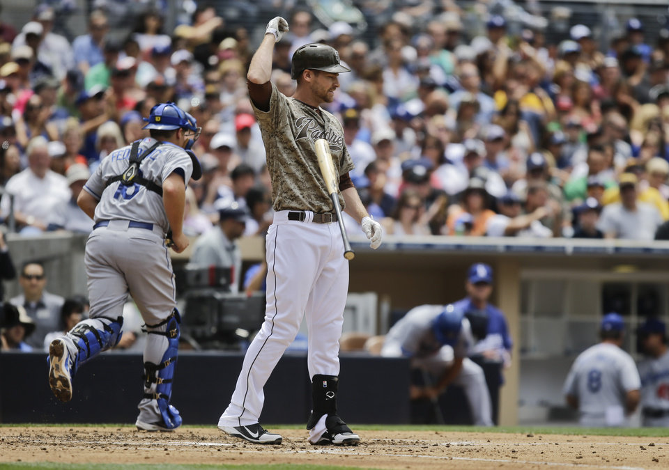 Photo - San Diego Padres' Chase Headley flips away his bat as Los Angeles Dodgers catcher Tim Federowicz heads for the dugout after Headley struck out to end the fourth inning of a baseball game in San Diego, Sunday, June 23, 2013. (AP Photo/Lenny Ignelzi)