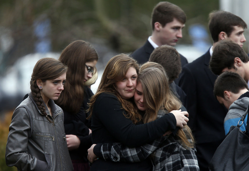 Photo - Mourners comfort one another as they leave a funeral service for 6-year-old Noah Pozner, Monday, Dec. 17, 2012, in Fairfield, Conn.  Pozner was killed when a gunman walked into Sandy Hook Elementary School in Newtown Friday and opened fire, killing 26 people, including 20 children. (AP Photo/Jason DeCrow)