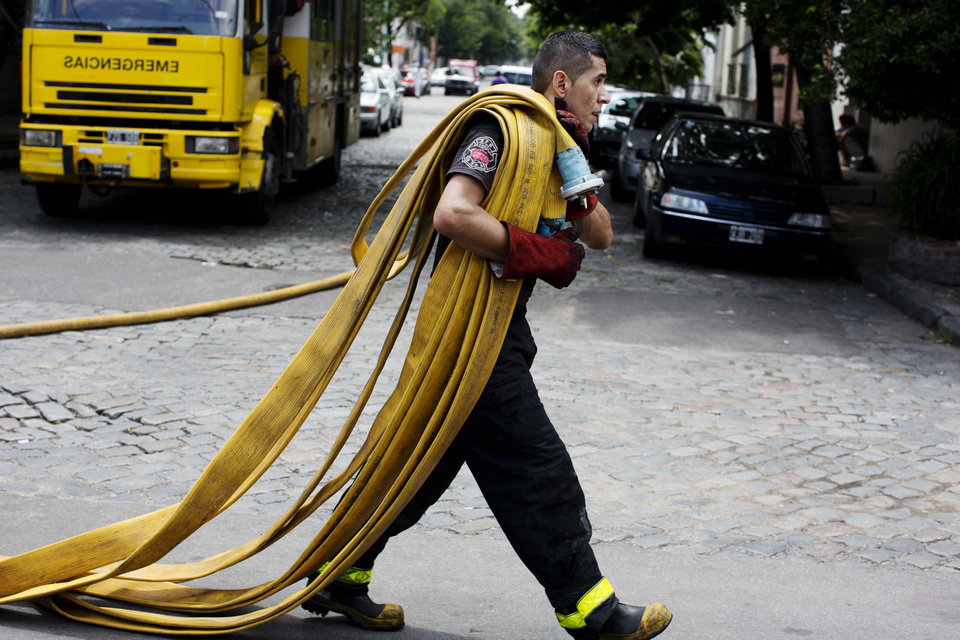 Photo - A firefighter carries a fire hose outside the Iron Mountain warehouse in Buenos Aires, Argentina, Wednesday, Feb. 5, 2014. Nine first-responders were killed in a fire that destroyed an archive of bank documents, according to authorities. (AP Photo/Rodrigo Abd)