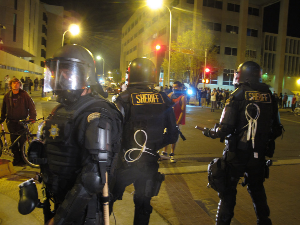 Photo - Riot police stand guard in front of protesters in downtown Albuquerque, N.M., Sunday, March 30,2014.  Hundreds of protesters marched past riot police in Albuquerque on Sunday, days after a YouTube video emerged threatening retaliation for a recent deadly police shooting. The video, which bore the logo of the computer hacking collective Anonymous, warned of a cyberattack on city websites and called for the protest march. (AP Photo/Russell Contreras)
