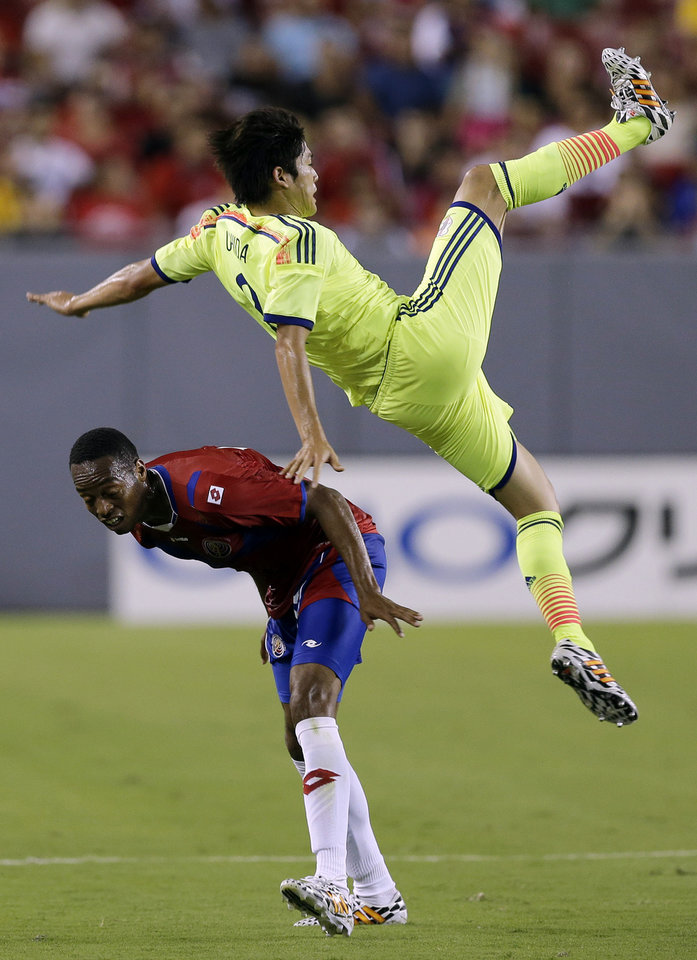 Photo - Japan defender Atsuto Uchida flies through the air after getting upended going up for a header by Costa Rica midfielder Celso Borges, left, during the first half of a friendly soccer match, Monday, June 2, 2014, in Tampa, Fla. (AP Photo/Chris O'Meara)