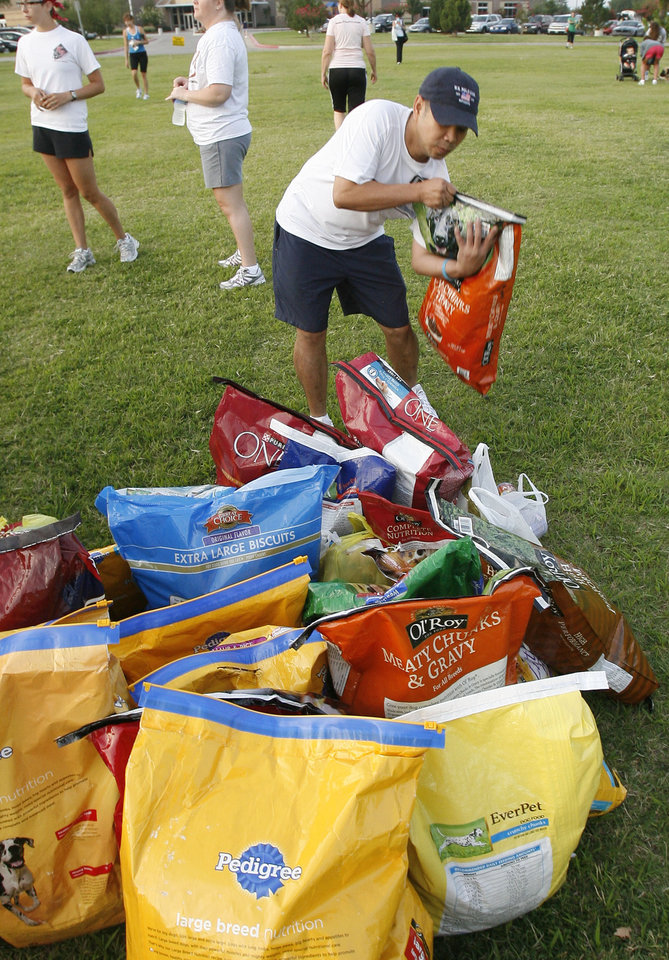 Photo - DONATE / DONATION: Paul Nguyen brings a bag of dog food to a free outdoor boot camp exercise class at Earlywine Park in Oklahoma City, OK, Saturday, Aug. 15, 2009. Participants brought dog food which will be donated to a couple of rottweiler & mastiff dog rescue groups. By Paul Hellstern, The Oklahoman ORG XMIT: KOD