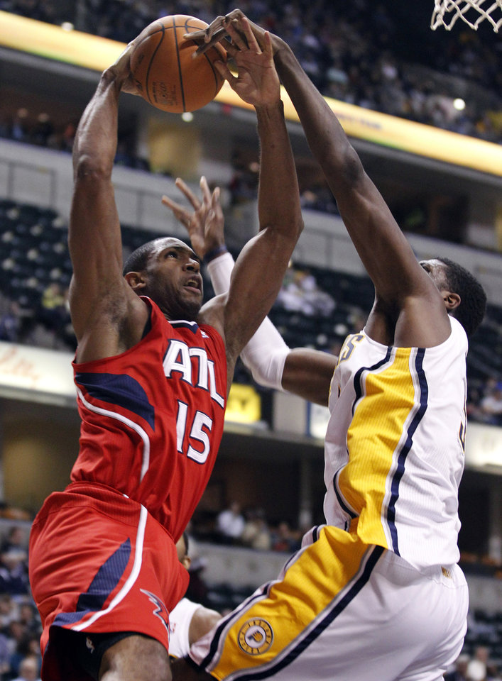 Photo -   Indiana Pacers center Roy Hibbert, right, blocks the shot of Atlanta Hawks center Al Horford during the first half of an NBA basketball game in Indianapolis, Wednesday, Jan. 11, 2012. Horford was injured on the play and left the game. (AP Photo/Michael Conroy)