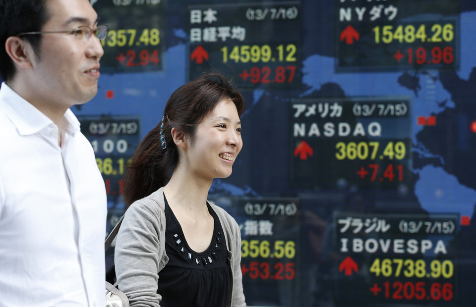 Photo - People walk by an electronic stock board in Tokyo, Tuesday, July 16, 2013.  Weaker-than-expected U.S. retail sales sent most Asian stock markets lower Tuesday as investors awaited congressional testimony from Federal Reserve chairman Ben Bernanke later in the week.(AP Photo/Shizuo Kambayashi)