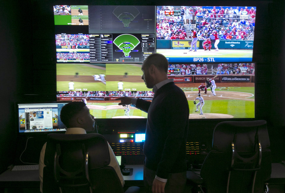 Photo - Two technicians work in a booth during a preview of Major League Baseball's Replay Operations Center, in New York, Wednesday, March 26, 2014. Less than a week before most teams open, MLB is working on the unveiling of its new instant replay system, which it hopes will vastly reduce incorrect calls by umpires. (AP Photo/Richard Drew)