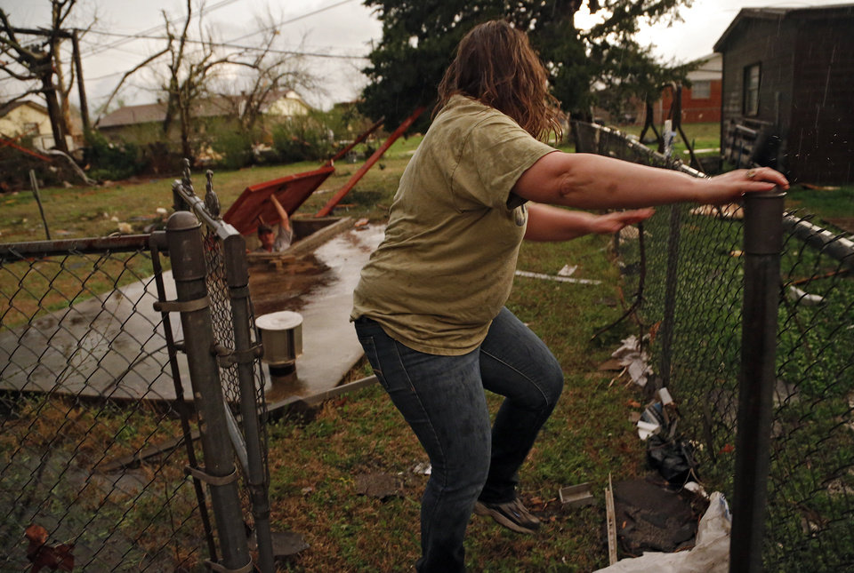 Photo - Linda Smith forces open the gate to reach her husband Jeff as he looks out of the storm shelter after a tornado hit in Moore, Okla. on Wednesday, March 25, 2015.  Photo by Chris Landsberger, The Oklahoman